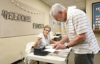 Randall Tomlinson (right) receives his ballot Tuesday, July 13, 2021, from Washington County election official Paula Burks at the Johnson Church of Christ in Johnson. Johnson residents well decide wether to OK a temporary 1% sales tax to back a $7.3 million street bond issue, according to the city's website. Check out nwaonline.com/210714Daily/ and nwadg.com/photos for a photo gallery.(NWA Democrat-Gazette/David Gottschalk)