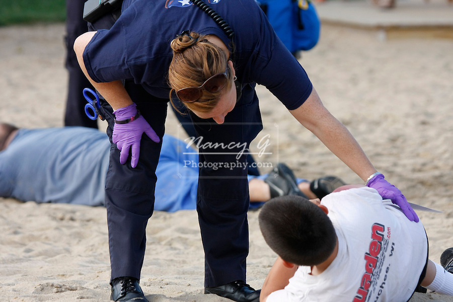 An EMT at a scene of a mass casulty incident is checking on one of the victims
