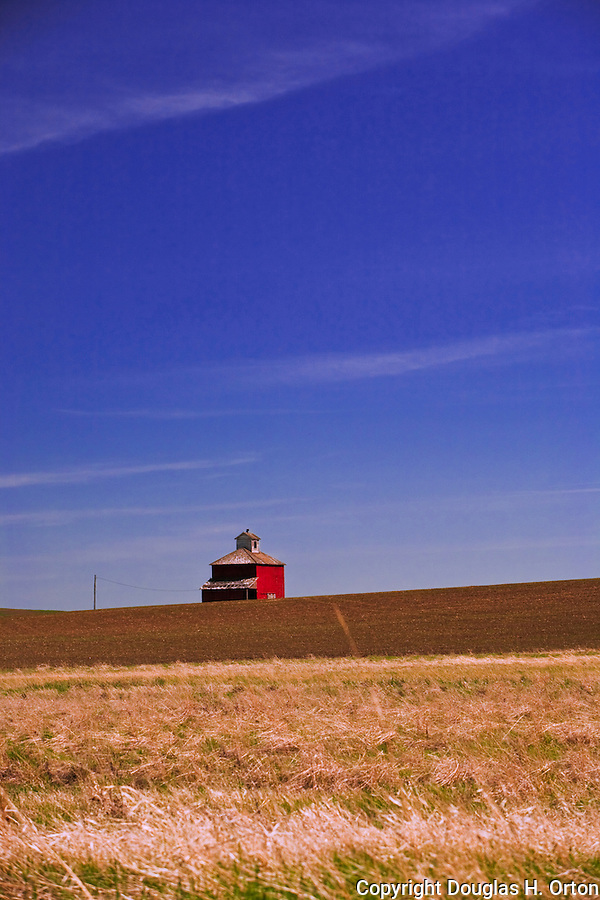 Distinctive lone cube barn between wheat fields in the Palouse Hills, WA, famous both as the breadbasket of the nation and as a landscape of beautiful rolling hills and family farms.  This large barn is dwarfed by the open terrain.