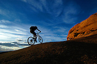 Mountain biker in silhouette climbing slickrock slope as the sun sets, Slick Rock Trail, Moab, Utah