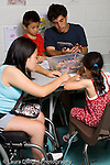 teenage volunteers working with young children at summer academy for children with special needs  vertical