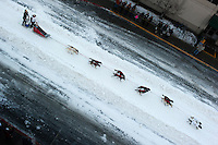 Dog teams sprint through city streets at the ceremonial start of the 2014 Iditarod Dogsled Race in downtown Anchorage, Alaska. Sixty-nine mushers paraded their teams through Anchorage today and will depart from the official start in Willow tomorrow to begin the 975-mile race to Nome.