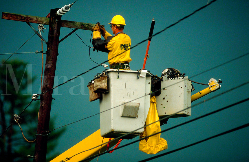Lineman standing in cherrypicker and wearing a hardhat repairs electric lines.