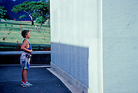 Child views names on wall honoring war veterans . National Cemetary of the Pacific, Punchbowl crater, Oahu