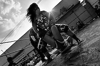 """A female Lucha libre wrestler locks her rival in a hold during a fight at a local arena in Mexico City, Mexico, 28 May 2011. Lucha libre, literally """"free fight"""" in Spanish, is a unique Mexican sporting event and cultural phenomenon. Based on aerial acrobatics, rapid holds and the use of mysterious masks, Lucha libre features the wrestlers as fictional characters (Good vs. Evil). Women wrestlers, known as luchadoras, often wear bright shiny leotards, black pantyhose or other provocative costumes. Given the popularity of Lucha libre in Mexico, many wrestlers have reached the cult status, showing up in movies or TV shows. However, almost all female fighters are amateur part-time wrestlers or housewives. Passing through the dirty remote areas in the peripheries, listening to the obscene screams from the mainly male audience, these no-name luchadoras fight straight on the street and charge about 10 US dollars for a show. Still, most of the young luchadoras train hard and wrestle virtually anywhere dreaming to escape from the poverty and to become a star worshipped by the modern Mexican society."""