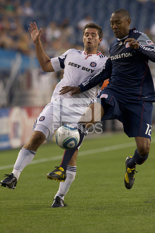 New England Revolution defender Cory Gibbs (12) gets between Chicago Fire midfielder Peter Lowry (8) before he can control the pass. The Chicago Fire defeated the New England Revolution, 1-0, at Gillette Stadium on June 27, 2010.