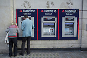 A man and a woman at a NatWest cash machine, London.
