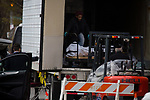 The body of a COVID-19 removed by forklift from a refrigerated trailer serving as a temporary morgue during the coronavirus pandemic (COVID-19) in front of New York Community Hospital in the Brooklyn borough of New York City on April 5, 2020.  Photograph by Michael Nagle