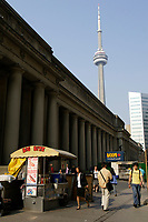 People going to work , early in the morning, walk beside a hot dog stand, on Front street  in downtown Toronto.....In the background :  Union Station and the CN Tower.......The CN Tower, located in Toronto, Ontario, Canada, is the world's tallest freestanding structure on land, standing 553.33 meters (1,815 ft 5 in) tall. It is considered the signature icon of the city, attracting more than two million international visitors annually....Photo : Pierre Roussel - Images Distribution
