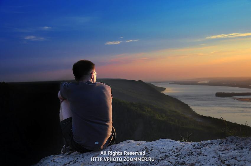 Boy enjoy sunset in Russian National Park sitting on a steep rock of Zhiguli mountains