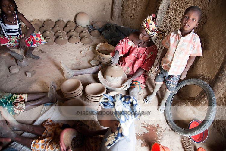 In the village of Kalabougou near Segou, Mali, women of the numu blacksmiths population have worked for centuries as traditional potters.  Numu women of the same family, often spanning several generations, work together in the household to prepare the pots for the kiln.