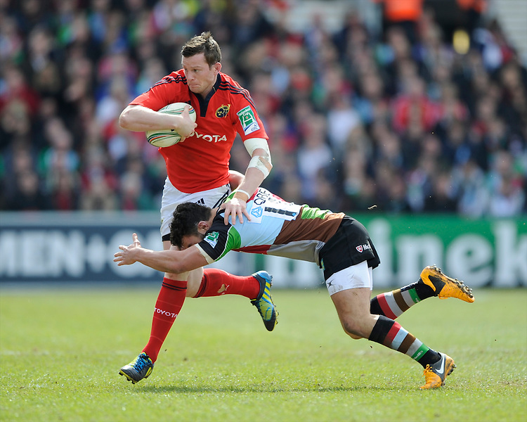 Denis Hurley of Munster Rugby is tackled by George Lowe of Harlequins during the Heineken Cup quarter final match between Harlequins and Munster at the Twickenham Stoop on Sunday 7th April 2013 (Photo by Rob Munro)