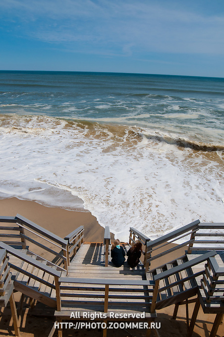 Two girls watch the waves sitting on stairs in Marconi beach, Cape Cod