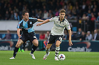 Tom Cairney of Fulham holds off Stephen McGinn of Wycombe Wanderers during the Capital One Cup match between Wycombe Wanderers and Fulham at Adams Park, High Wycombe, England on 11 August 2015. Photo by Andy Rowland.