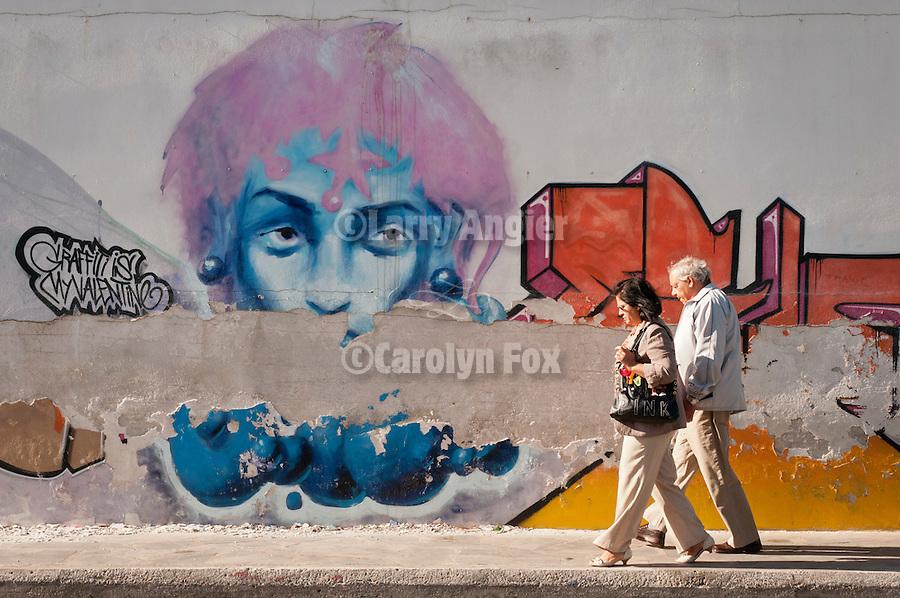 A couple walks by an art-covered wall along a street, Ermoupoli, Syros, Cycledes, Greece