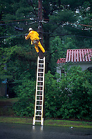 Electric utility lineman on ladder working on power lines in rain.
