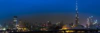 Twilight skyline panorama with the Burj Khalifa, downtown skyscrapers, and wave-shaped Meydan Bridge in the Emirate of Dubai, Asia