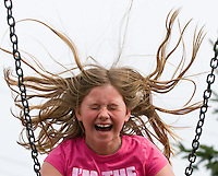 A young girl's hair flies in the wind as she reaches apogee on the swing set at a park in Westerville, Ohio. Photo Copyright Gary Gardiner. Not be used without written permission detailing exact usage.