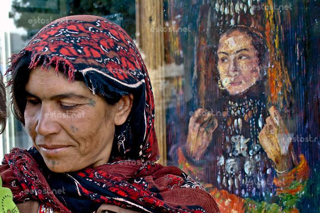 AFGHANISTAN, 06.2008, Kabul. Strassenbettlerin vor einem Schaufenster mit Portraitbildern. | Beggar in the street in front of a shop window filled with portrait paintings.<br /> © Marzena Hmielewicz/EST&OST