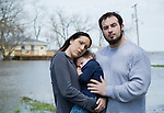 Parents with son standing in flooded town