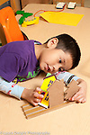 Education preschool 3-4 year olds boy playing by himeslf with wooden house block pieces talking to himself