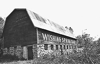 Courtesy BV Historical Museum The Wishing Spring Gallery got its start in 1982, when the Village Art Club, under the leadership of artist and wood carver Paul Parish, acquired the old Linebarger dairy barn (pictured here) from Cooper Communities for a headquarters and gallery. The old barn was cleaned out and refurbished, opening as the Wishing Spring Gallery, 35 years ago this summer in 1984. Paul Parish is also the one who saved the old log cabin, which was originally built in the early 1900's on the site just inside the Highlands Gates at the corner of Glasgow Blvd. and Timbercrest Lane. He moved it to his property near Lake Avalon in 1974 to serve as his personal art gallery.That cabin is now the Settlers Cabin sitting on the grounds of the Bella Vista Historical Museum.