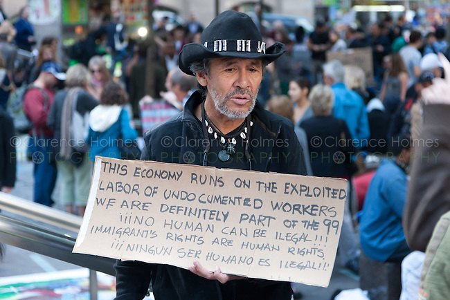 A man holds a protest sign in Zuccotti Park expressing concern for undocumented workers and immigrants during the Occupy Wall Street demonstration in New York City, New York.