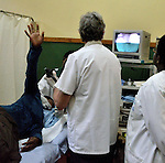 A patient raises her hand in pain during an endoscopy procedure preformed by a Belgian doctor from the group DDK at Gisenyi Community Hospital in northwest Rwanda..