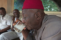 Nigeria. Enugu State. Agbani. An elderly black african man drinks a glass of palm wine, which is an alcoholic beverage created from the sap of various species of palm tree such as the palmyra, date palms, and coconut palms. 3.07.19 © 2019 Didier Ruef