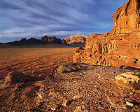Sandstone mountains rise from the desert sands in warm evening light in Wadi Rum, Jorda