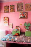 The walls of this simple bedroom are decorated with pictures of Indian deities