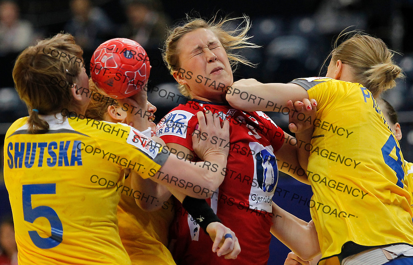 BELGRADE, SERBIA - DECEMBER 08: Marit Malm Frafjord (C) of Norway is challenged by Iryna Shutska (L) and Anastasiia Pidpalova (R) of Ukraine during the Women's European Handball Championship 2012 Group A match between Norway and Ukraine at Arena Hall on December 08, 2012 in Belgrade, Serbia. (Photo by Srdjan Stevanovic/Getty Images)