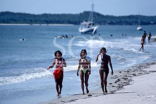 Itaparica Island, Brazil. Three mulatta girls walking on a beach with a yacht behind. Bahia State.
