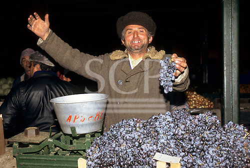 Bucharest, Romania. Man with two gold teeth selling black grapes.