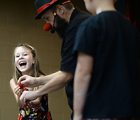 Jadeyn Paredes, 7, (left) of Prairie Grove reacts Wednesday, July 21, 2021, as George Reader, a magician from Bella Vista, pulls two clown noses from her hands that did not appear to be there earlier during a performance at the Prairie Grove Public Library. The show was the finale for the library's summer reading program. Visit nwaonline.com/210722Daily/ for today's photo gallery.<br /> (NWA Democrat-Gazette/Andy Shupe)