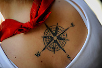 A compass rose tattooed on the back of a young woman is seen during the San Fermin Festival, on July 8, 2012, in Pamplona, northern Spain. The festival is a symbol of Spanish culture that attracts thousands of tourists to watch the bull runs despite heavy condemnation from animal rights groups . (c) Pedro ARMESTRE