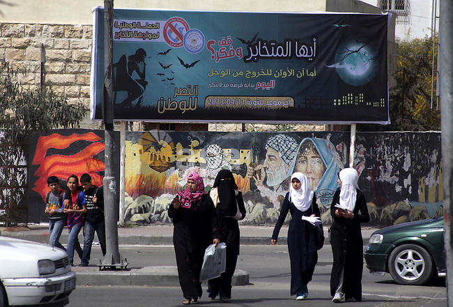 """Palestinian students walk past a banner in Gaza City announcing the launch of a campaign against collaborating with Israel on March 13, 2013, as the ruling Hamas launches a month-long campaign to encourage """"collaborators"""" with Israel to repent. Photo by Ashraf Amra"""