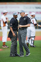 Base umpire Thomas Burrell (right) discusses a call with home plate umpire Grant Hinson during the Coastal Plain League game between the Gastonia Grizzlies and the Asheboro Copperheads at McCrary Park on June 1, 2015 in Asheboro, North Carolina.  The Copperheads defeated the Grizzlies 11-6. (Brian Westerholt/Four Seam Images)