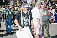 """Ryan Deame wears VR goggles and holds a sign reading """"Stop Hate / Donate / TheTrevorProject.org,"""" as he marches in the Straight Pride Parade in Boston, Massachusetts, on Sat., August 31, 2019. The parade was organized in reaction to LGBTQ Pride month activities by an organization called Super Happy Fun America. The Trevor Project is an NGO focused on preventing suicide among LGBTQ youth."""