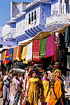 India, Rajasthan, Pushkar: Local women walking past colourful shops in main street