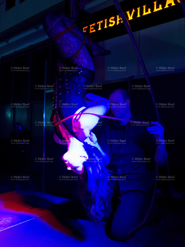 """Switzerland. Canton Ticino. Lugano. Couple and bondage. The woman is tied and upside down. Bondage or ligotage is consentually tying, binding, or restraining a partner for erotic, aesthetic, and/or somatosensory stimulation. Rope, cuffs, bondage tape, self-adhesive bandages, or other restraints may be used for this purpose. Bondage itself does not imply sadomasochism. Bondage may be used as an end into itself, as in the case of rope bondage and breast bondage. It may also be used as a part of sex or in conjunction with other BDSM activities. The letter """"B"""" in the acronym """"BDSM"""" comes from the word """"bondage"""". Sexuality and erotica are an important aspect in bondage, but are often not the end in itself. Aesthetics also plays an important role in bondage. A common reason for the active partner to tie up their partner is so both may gain pleasure from the restrained partner's submission and the feeling of the temporary transfer of control and power. For sadomasochistic people, bondage is often used as a means to an end, where the restrained partner is more accessible to other sadomasochistic behaviour. However, bondage can also be used for its own sake. The active partner can derive visual pleasure from seeing their partner tied up, and the restrained partner can derive tactile pleasure from the feeling of helplessness and immobility. Extasia 2014 is the first erotic and sex fair in southern Switzerland. 1.02.14 © 2014 Didier Ruef"""