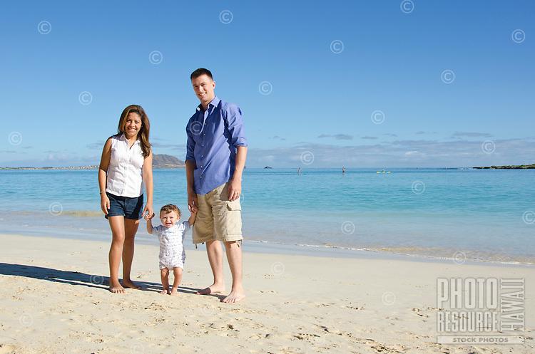 Portrait of parents and infant son on Kailua beach, O'ahu