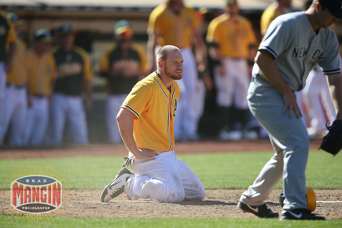 OAKLAND, CA - JUNE 13:  Brandon Moss #37 of the Oakland Athletics kneels in the dirt after being tagged out at home plate by New York Yankees catcher Chris Stewart #19 in the bottom of the 15th inning during the game at O.co Coliseum on Thursday June 13, 2013 in Oakland, California. Photo by Brad Mangin