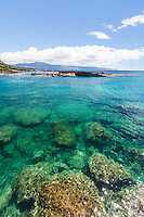 Distant snorkelers in clear water at Shark's Cove, North Shore of O'ahu.