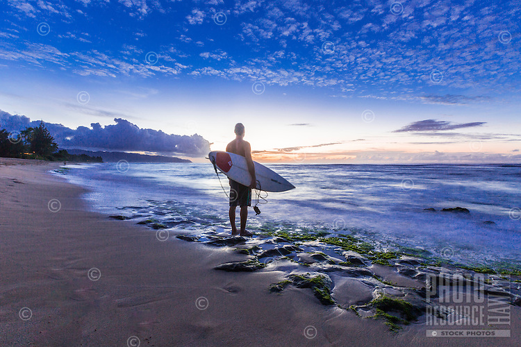 A surfer enjoys the last of the sunset after a surf session on the North Shore of O'ahu.