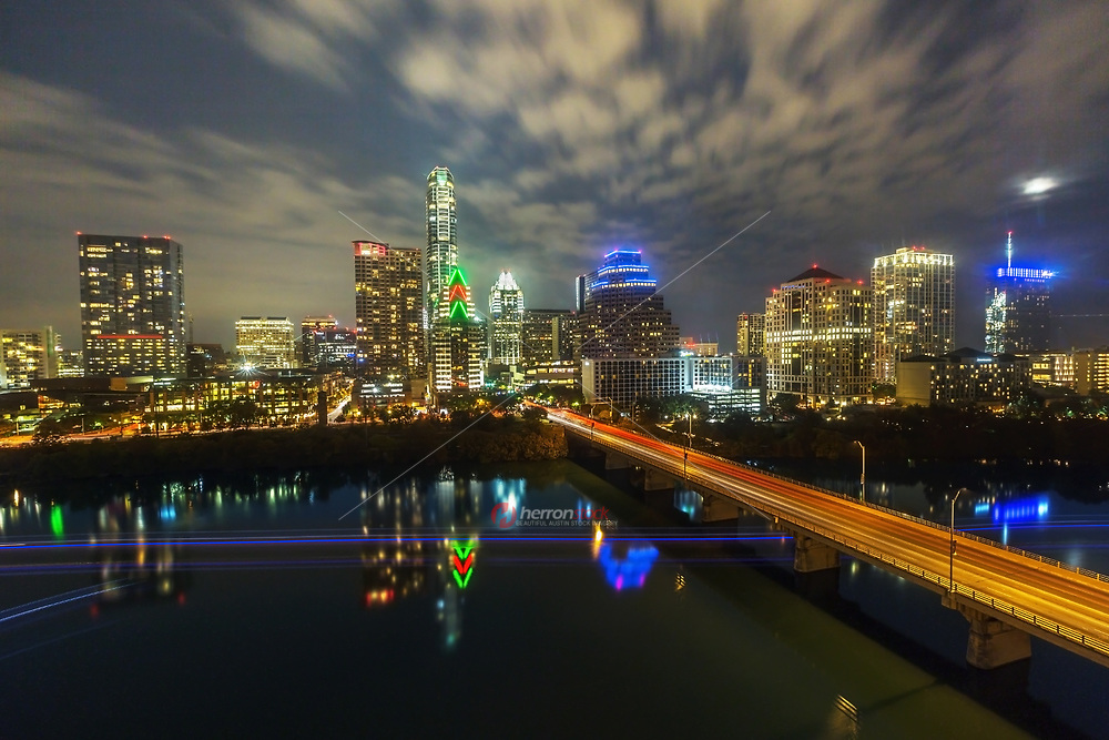 Christmas in Austin. Seasonal lights decorate the downtown Austin towers and skyline as fridged temperatures settle in for the night over Lady Bird Lake and the Congress Avenue Bridge.