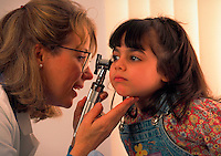 Doctor examining the ear of a young patient during a check-up.