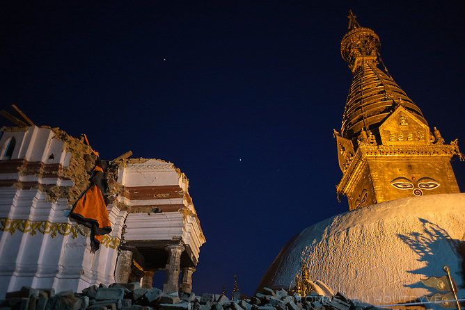 A 17th century shikhar temple destroyed by earthquake, left, is seen in front of the Swayambhunath stupa, right, in Kathmandu, Nepal in June 2015.