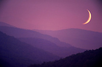 A crescent moon rises over a mountain range. Bennington, Vermont.