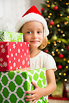 Girl (6-7) holding stack of Christmas presents